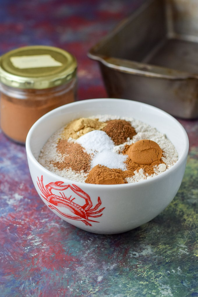 Cinnamon, ginger, cloves and nutmeg in a bowl of flour with a big jar of cinnamon in the background and a bread pan
