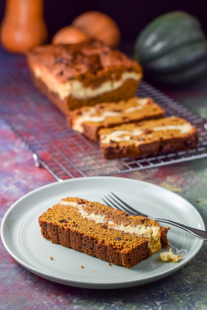 A plated piece of pumpkin bread with the cheesecake layer showing. There is the sliced bread in the background