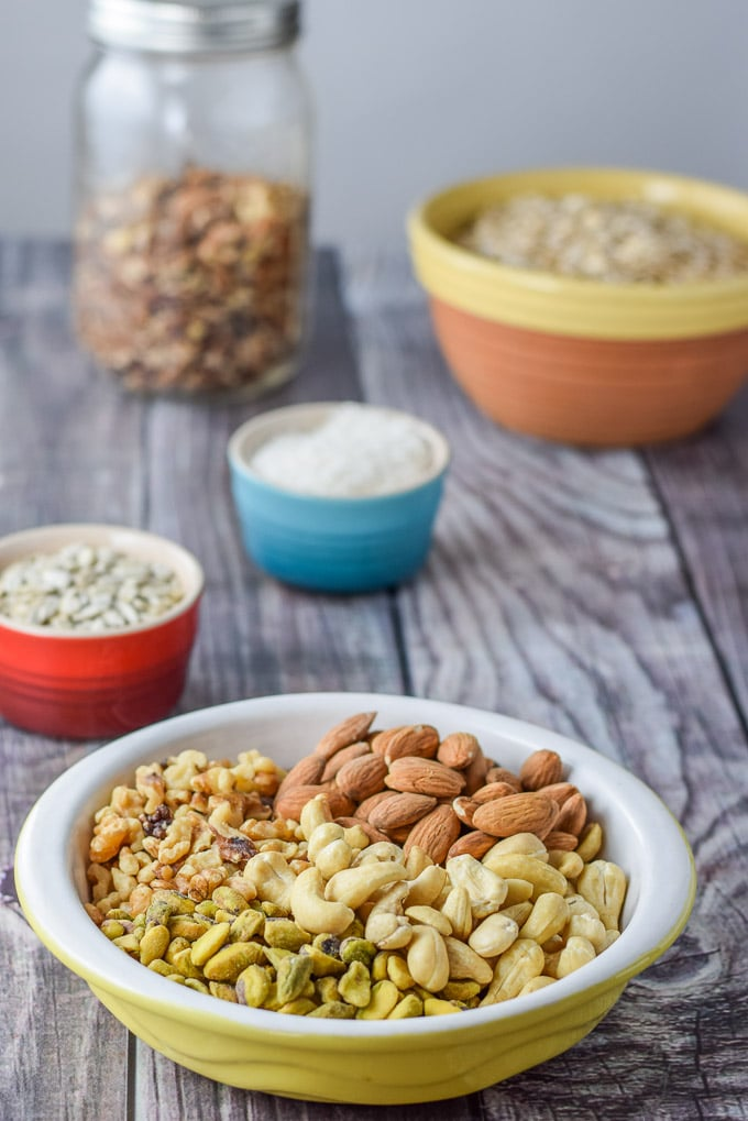 Pistachio, cashews, walnuts, almonds, sunflower seeds, coconut, pecans and oats on a grey wood background