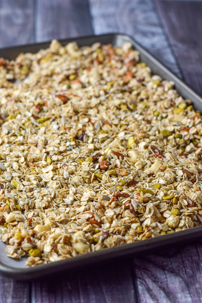 All the granola ingredients mixed and on the pan covered with parchment paper