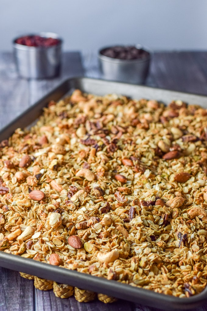 The granola baked and cooling on the table with some chocolate chips and cranberries in the background.