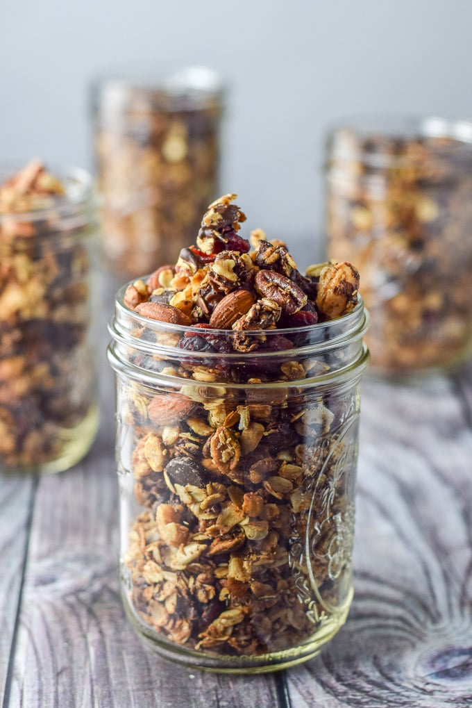 Close up of a jar filled with cranberry granola with the other jars in the background