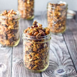 A bunch of jars filled with granola on a grey table - square