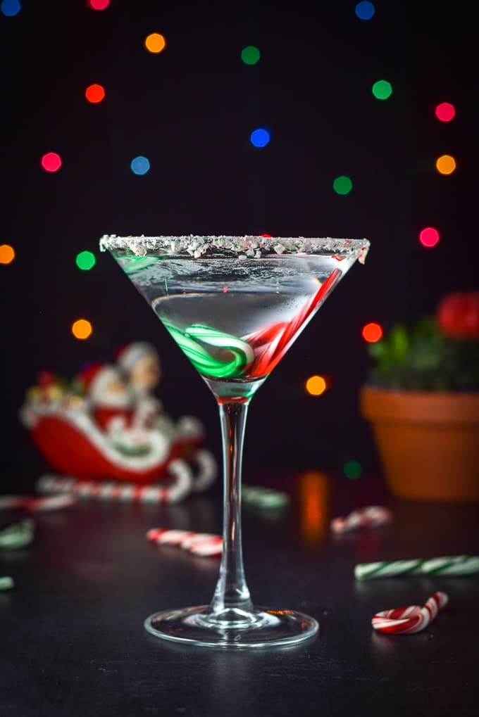 Vertical view of candy cane martini with the sled with santa and mrs claus in it