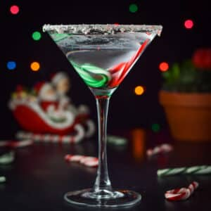 Vertical view of the martini with lights, santa claus in a sled and candy canes on the table - square
