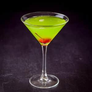A maraschino cherry dropped into the green midori cocktail - square