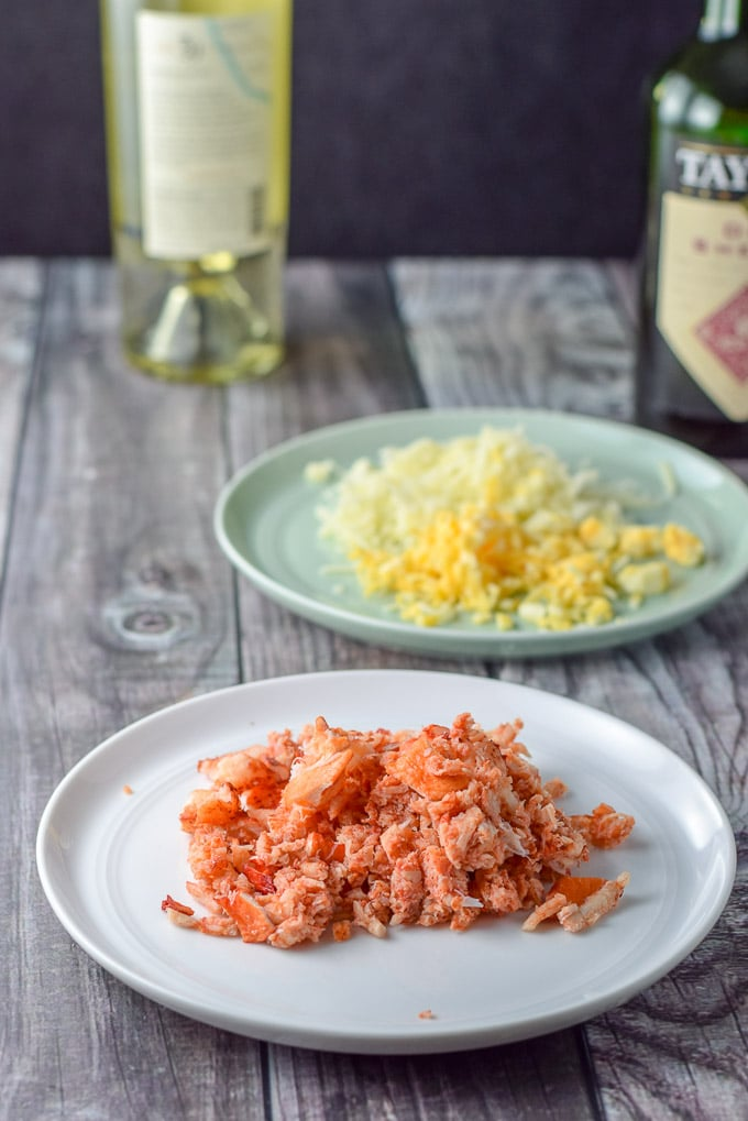 Lobster meat cut up, shredded cheese, sherry and wine in the background