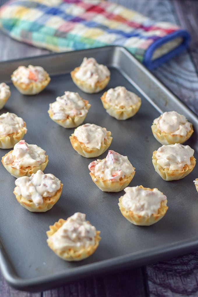 Filled phyllo tart shells with the cream cheese lobster mix on a jelly roll pan