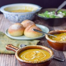 two bowls of scrumptious squash soup with rolls in the background