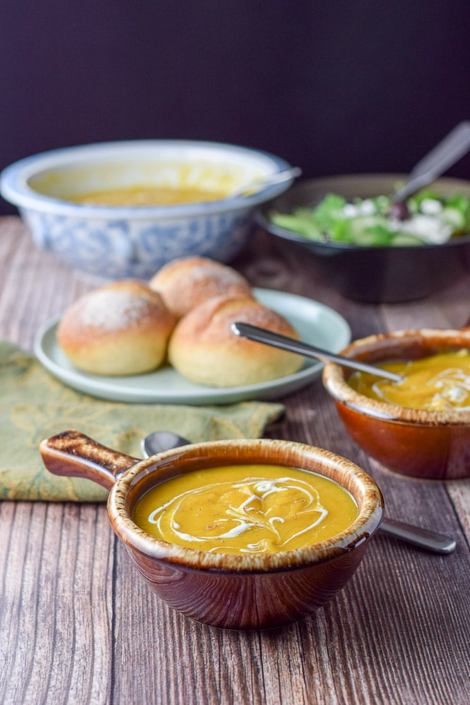 two bowls of squash soup with rolls in the background