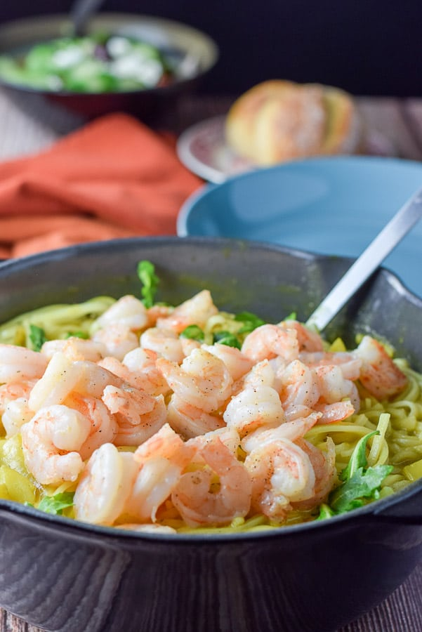 Shrimp piled on the noodles in a pan with a plate, roll and salad in the background