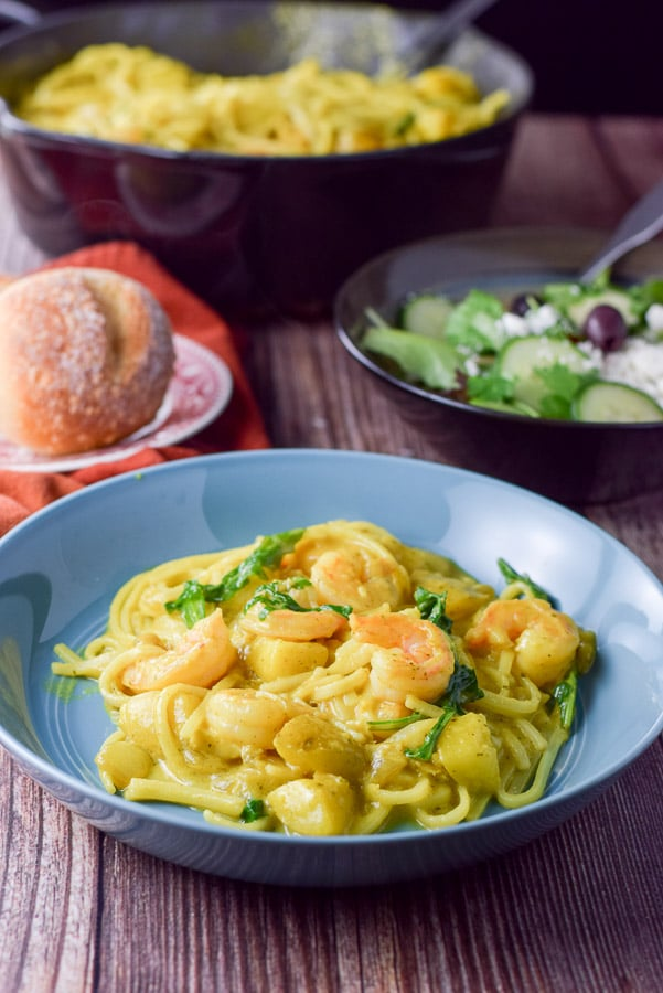 A blue bowl with shrimp on noodles in front of the pan, salad and roll