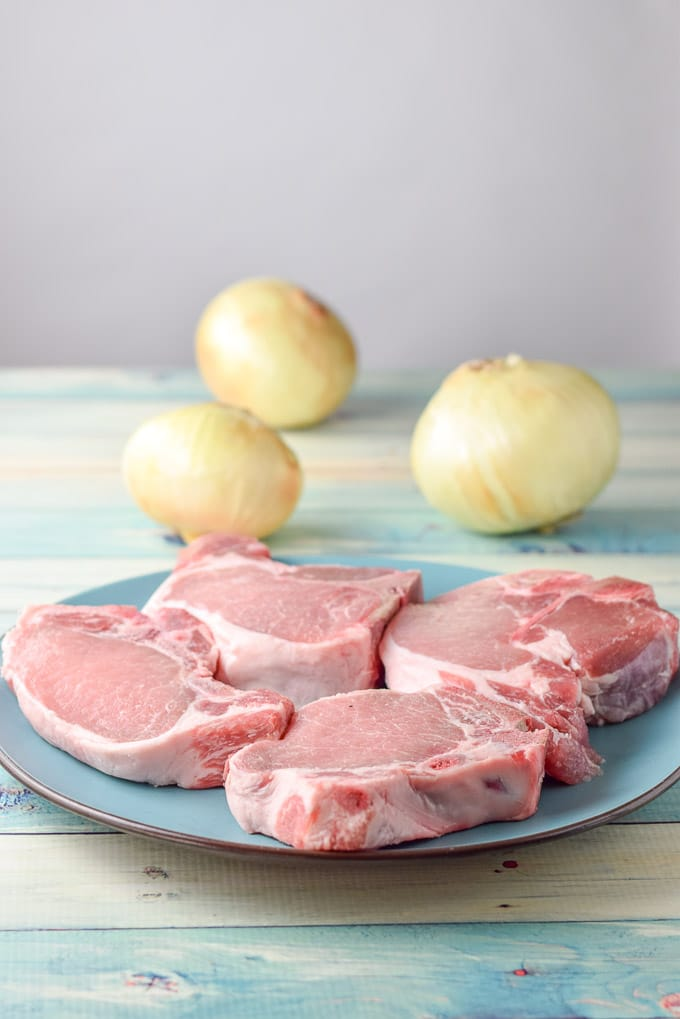 Four pork chops on a plate with some onions in the background for the moist pork chops