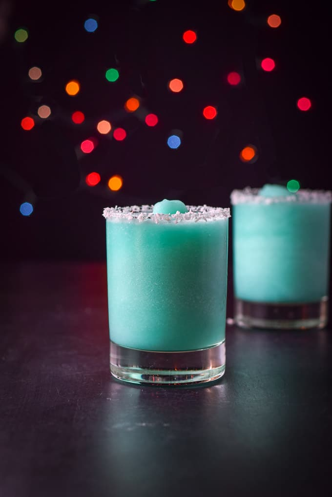 Vertical view of the frozen blue cocktails with coconut rims and lights in the background