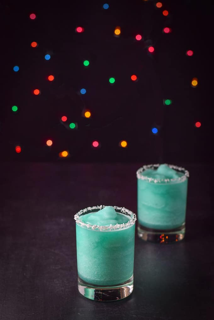 Two Jack Frost cocktails with coconut rims on a black table and colorful lights behind them