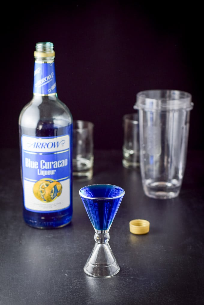 Blue Curacao poured out with the bottle, blender and glassware in the background