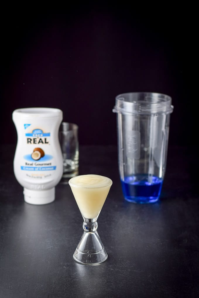 Cream of coconut poured out with the bottle, blender container and glass in the background