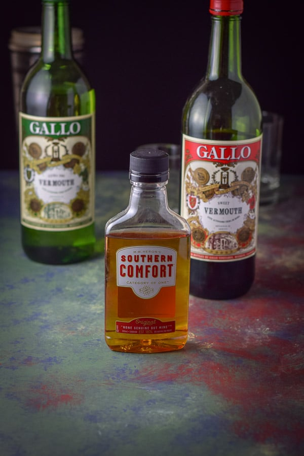 Southern Comfort, sweet vermouth, dry vermouth on a very colorful table