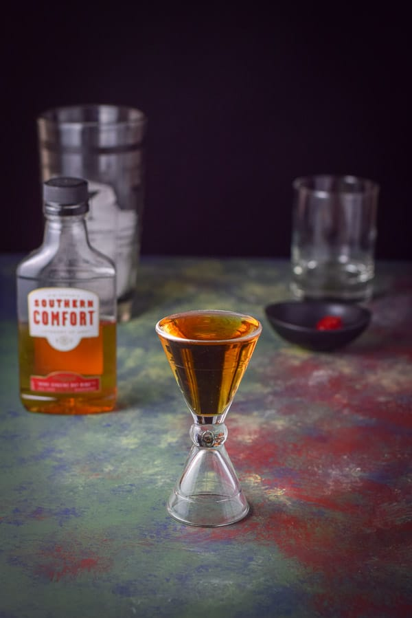 Southern Comfort poured out in a hour glass jigger with the bottle, shaker and glass in the background