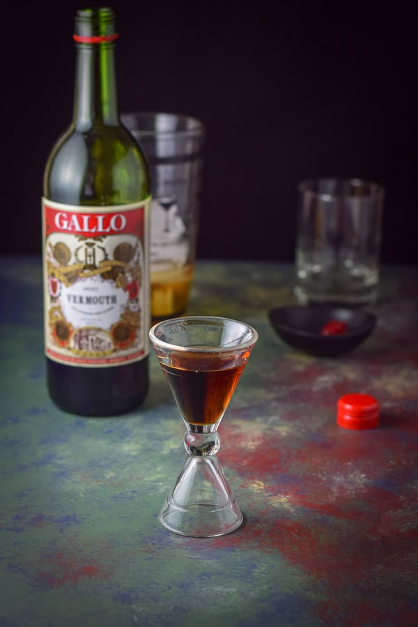 Sweet vermouth poured out in the jigger with the bottle, shaker, garnish and glass in the background