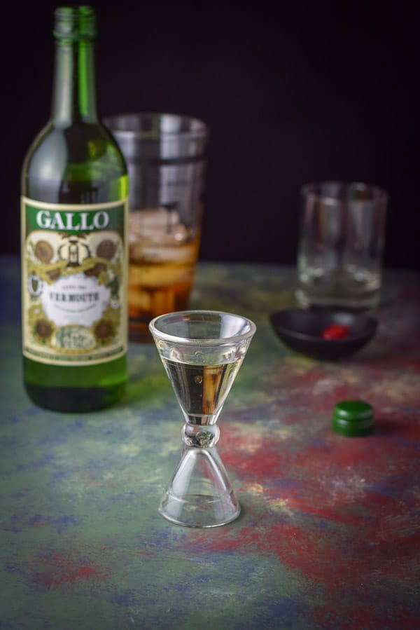 Dry vermouth measured in a glass jigger with the bottle, garnish, shaker and glass in the background