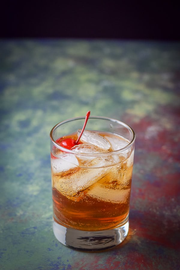 Close up of the ice filled double old fashioned glass with the Manhattan and a cherry