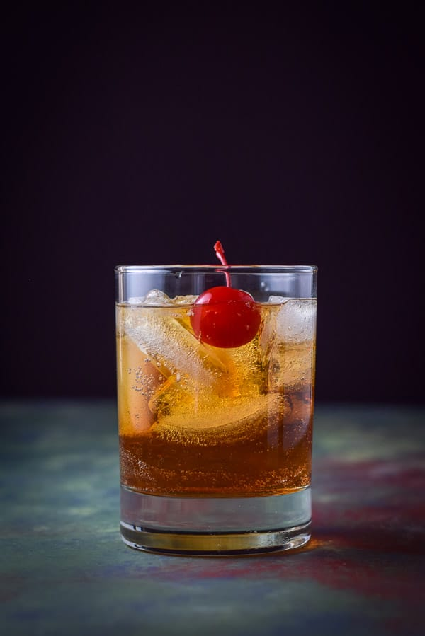 Vertical view of southern comfort Manhattan with the cherry in the front of the ice cubes