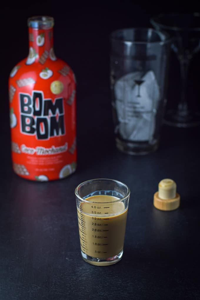 Bom Bom coco mochanut poured out with the bottle, shaker and glass in the background
