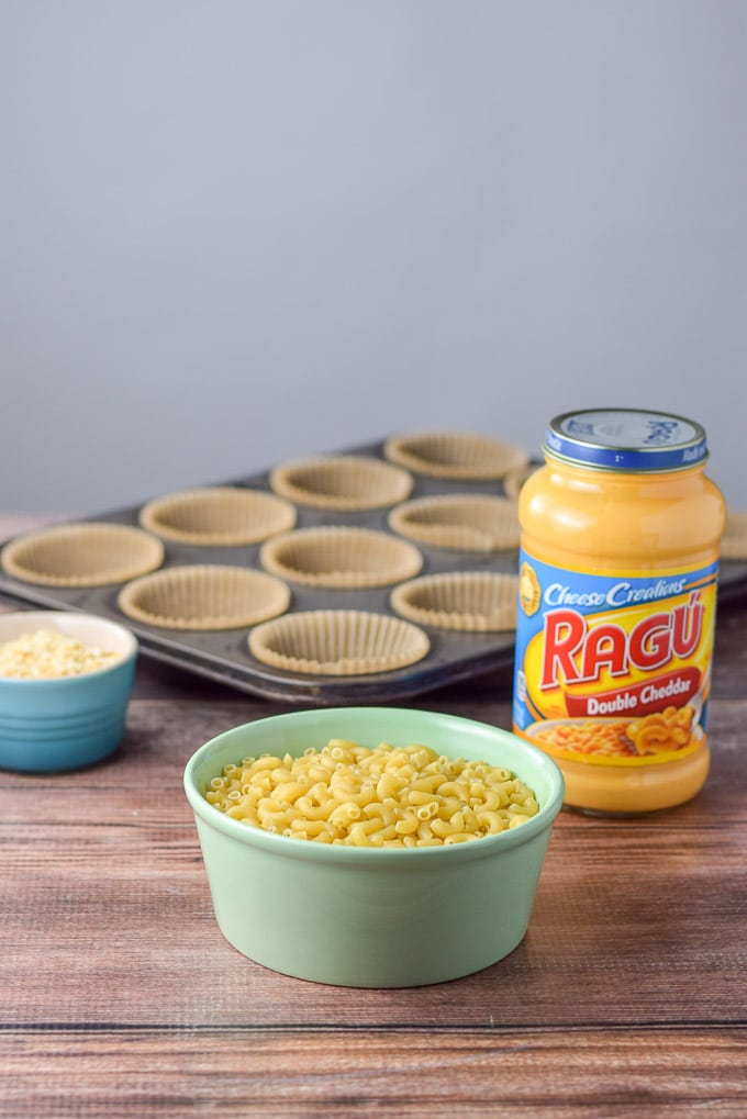 Elbow macaroni, cheddar sauce and muffin tins in the background