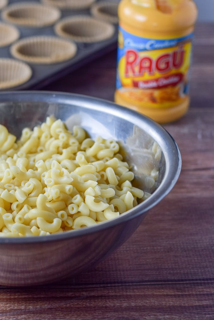 Elbow Macaroni cooked, and cheese sauce in the background with muffin tins