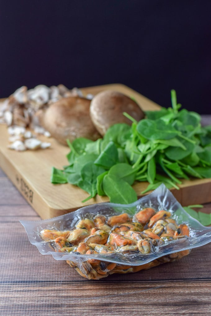Mussels in a package on the table and spinach and mushrooms on a wooden board in the background