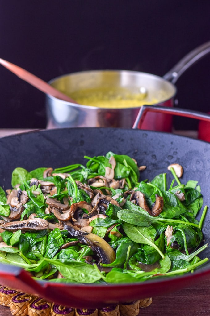 Mushrooms and spinach cooked in a wok with a pan of polenta in the background