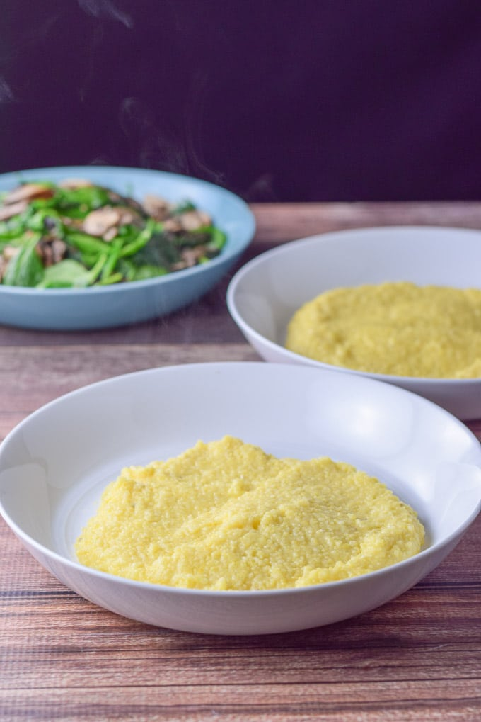 Polenta spooned in two bowls with some mushrooms and spinach in the background