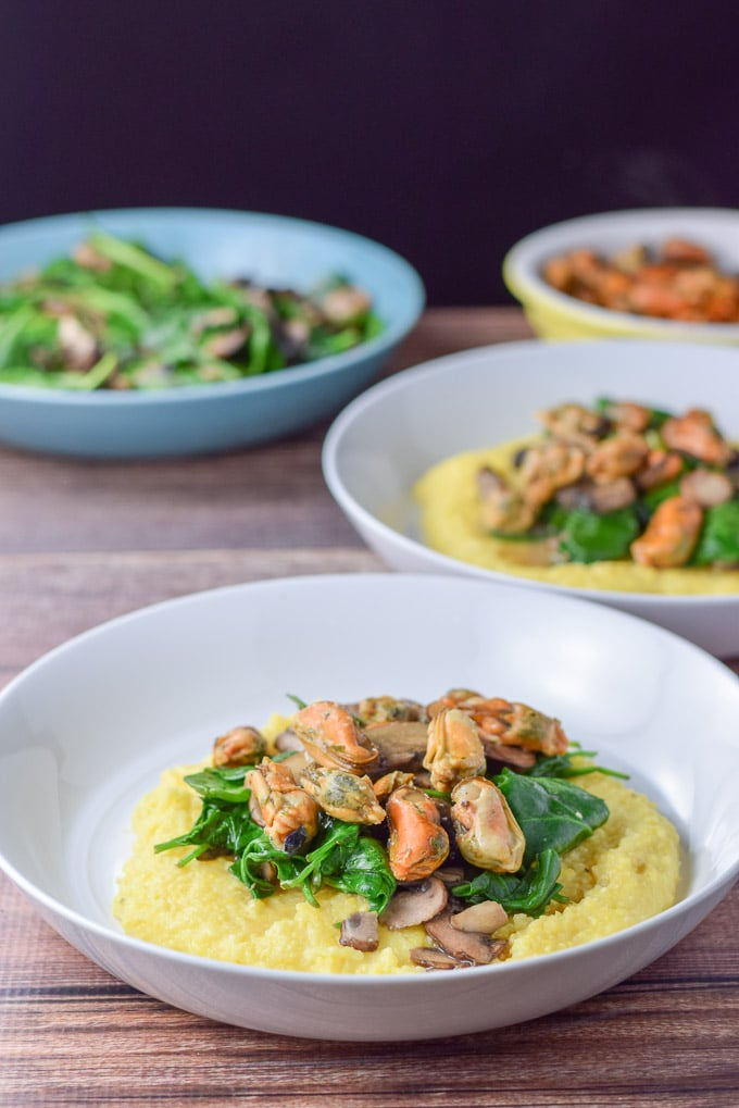 Two white shallow bowls of polenta topped with mushrooms, spinach and mussels