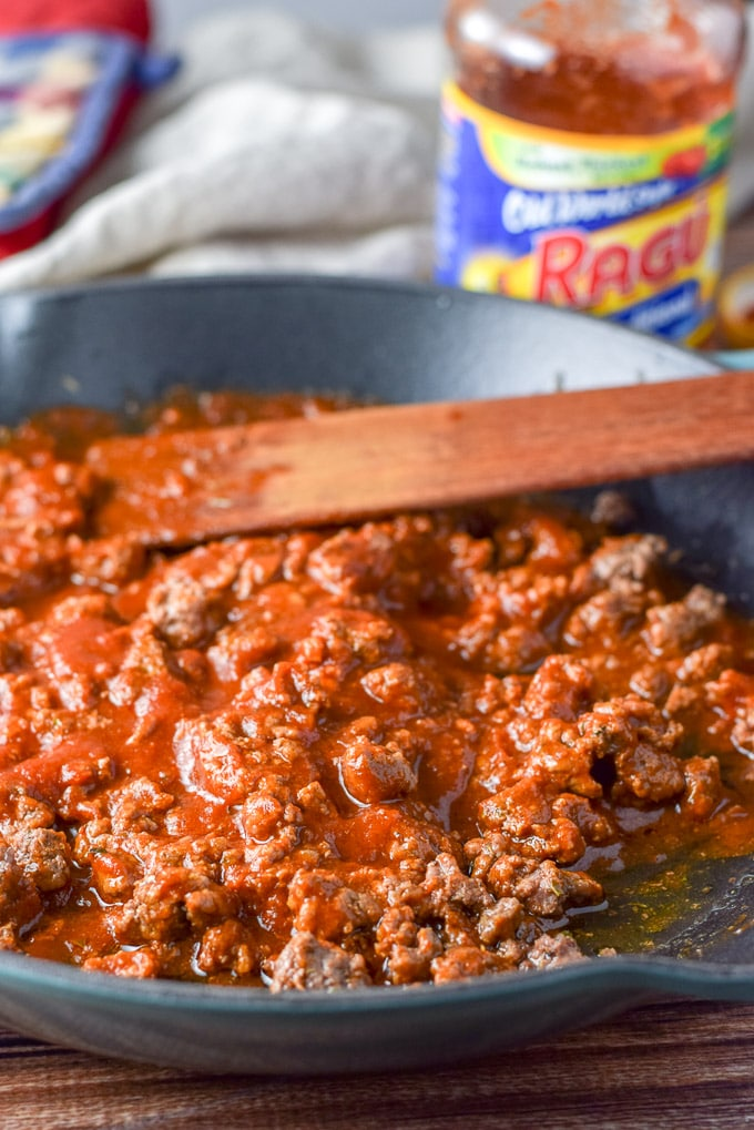 The red sauce mixed in with the pan of ground beef
