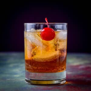Square photo of the double old fashioned glass filled with the Manhattan with a cherry floating in it