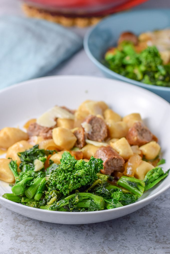 A close up view of the broccoli in a plate with some sausage and gnocchi