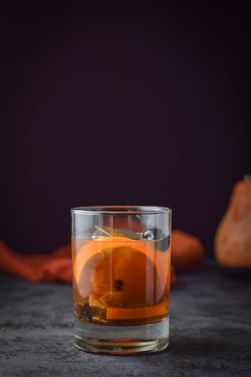 Vertical view of the classic double old fashioned glass with the cocktail and garnish in it