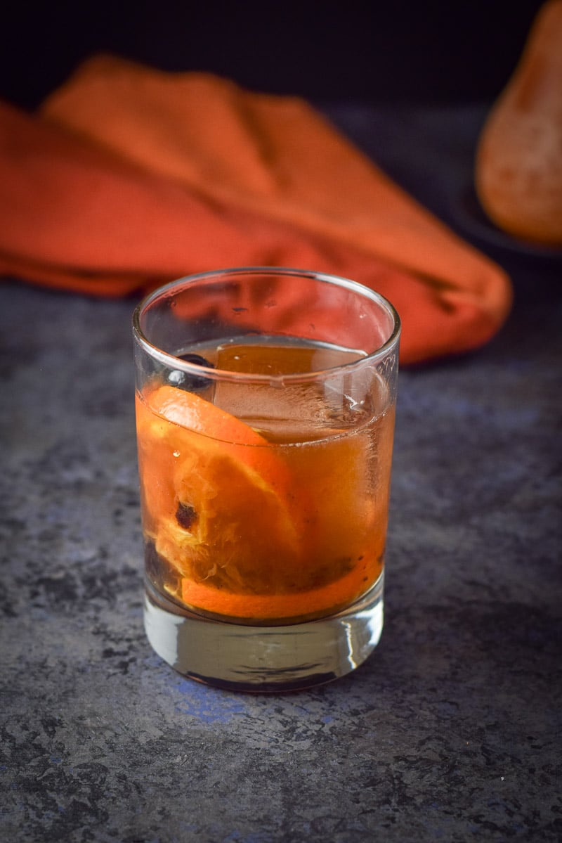Bourbon poured in the rocks glass with a big ice cube and orange and cherries