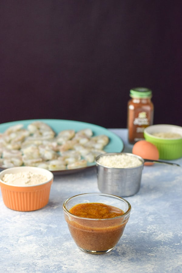 Apricot dipping sauce made, panko bread crumbs, spelt flour, an egg and shrimp on a blue table