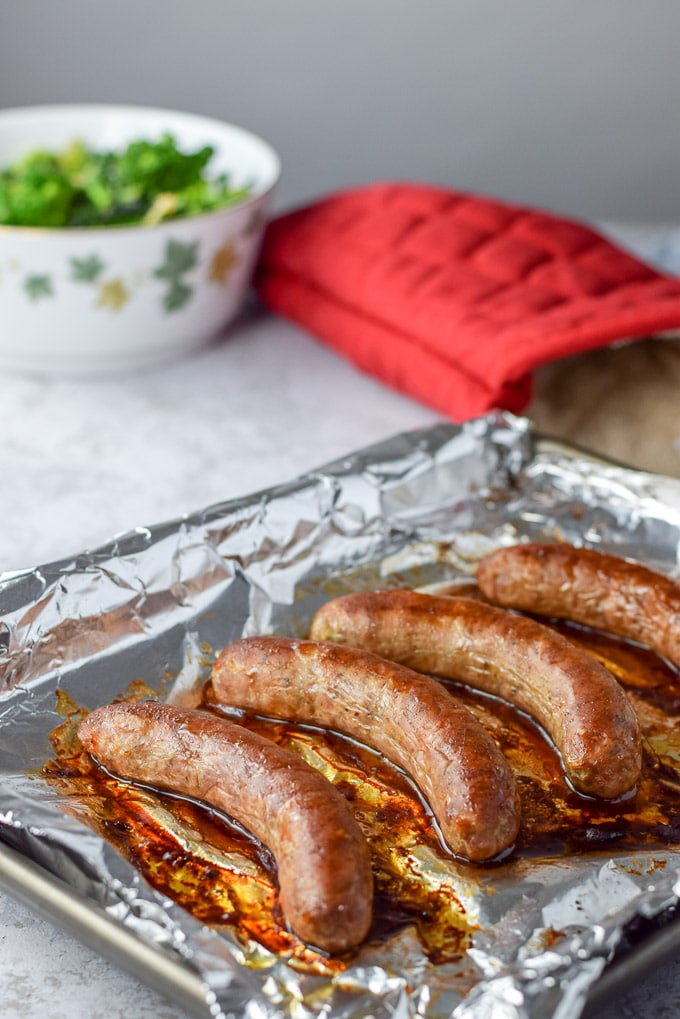 Sausage baked on a tray with cooked broccoli in the background