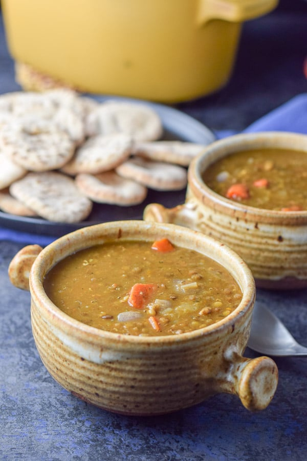 Closer look of the 2 crocks of lentil soup with a plate of pita rounds and more soup in the background