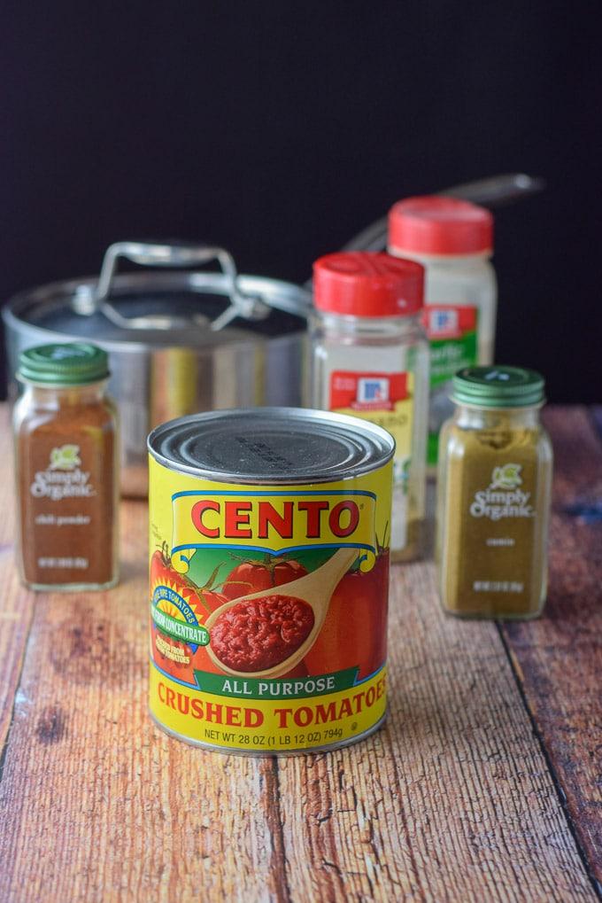 Crushed tomatoes, cumin, chili powder, oregano, garlic powder and a pan in the background