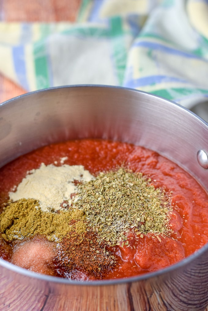Crushed tomatoes in a pan with oregano, chili powder, cumin, salt and garlic powder added on top