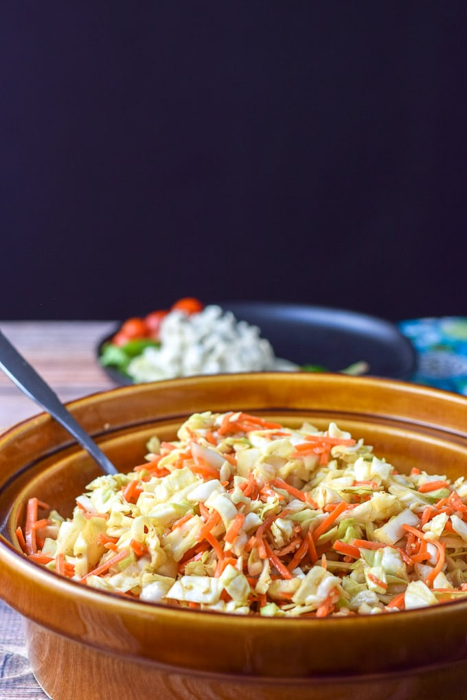 coleslaw mixed in a big brown bowl with a black plate with some lunch on it in the background