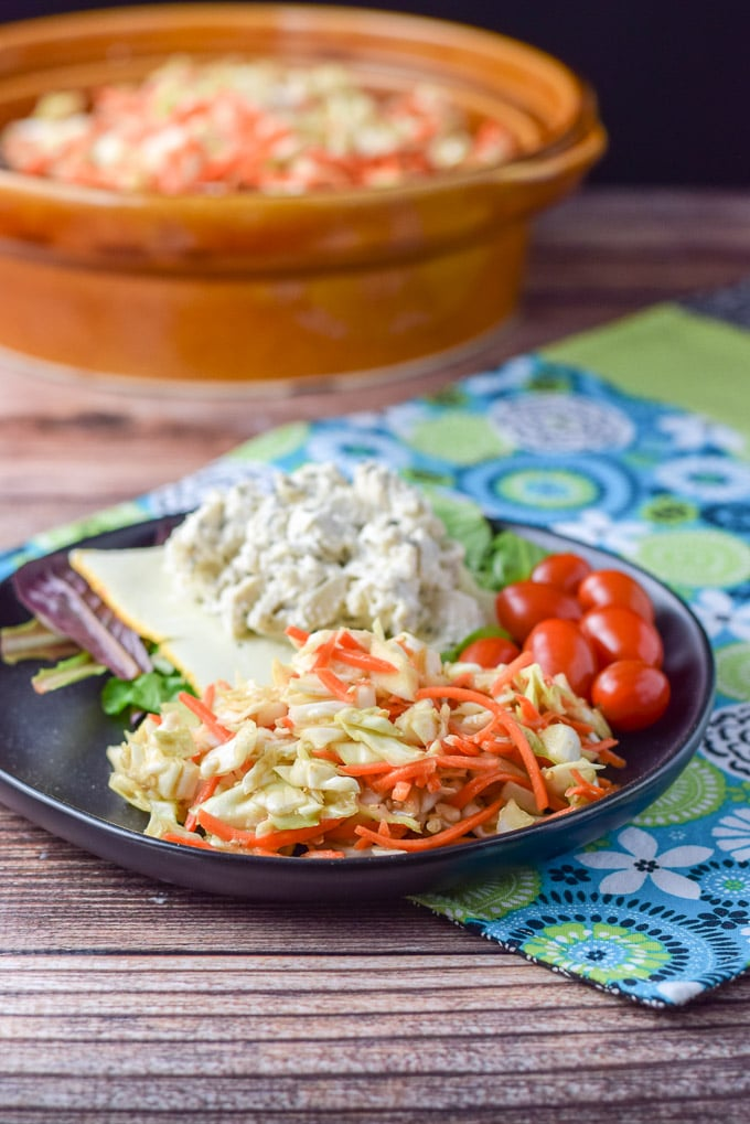 A black plate with coleslaw, chicken salad, munster cheese, lettuce and some grape tomatoes with the big brown bowl of slaw in the background