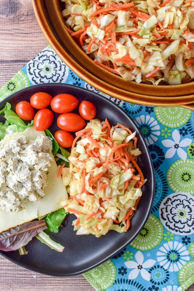 Overhead view of the coleslaw on a plate with chicken salad, munster cheese, lettuce and some grape tomatoes and the brown bowl with the slaw in the upper corner