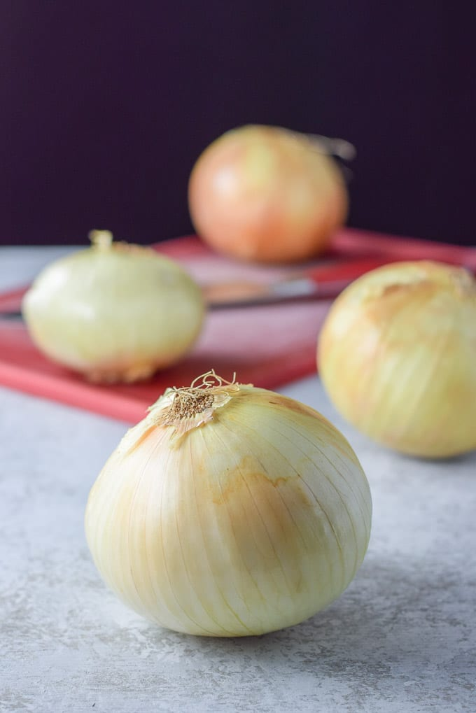 Onions on a board and a knife on the red cutting board