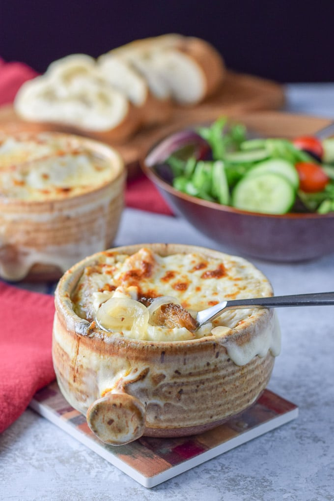 A spoon is in the crock of cheesy onion soup with a salad and sliced bread in the background