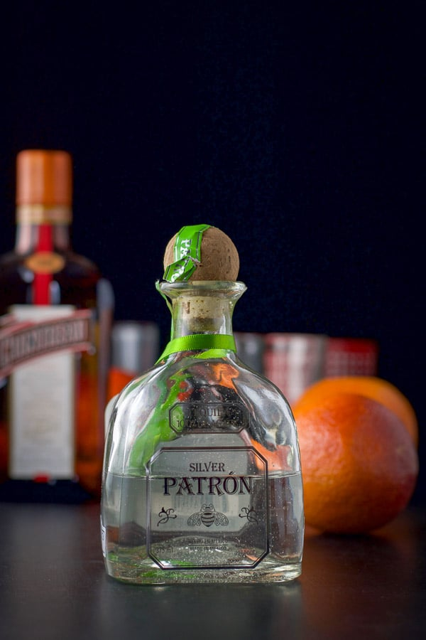 Patron silver tequila, cointreau, and blood oranges on a black table